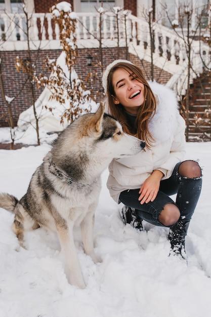 Modische freudige junge frau, die spaß mit reizendem husky hund im schnee auf der straße hat. wahre gefühle, glückliche momente im winter, lächeln, positivität ausdrücken. Kostenlose Fotos