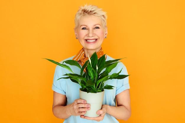 Modische gut aussehende dame mit kurzem gefärbtem haar, das gegen gelben hintergrund aufstellt, der topfblume hält. reife frau, die zimmerpflanze wächst und ruhestand genießt. menschen-, botanik- und häuslichkeitskonzept Kostenlose Fotos