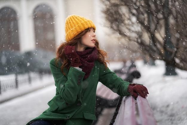 Modische junge frau, die draußen in einer stadtstraße aufwirft. winterporträt im freien, im schneefall Premium Fotos