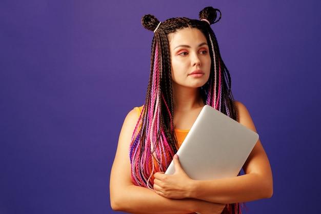 Modische junge studentin mit langen afro-zöpfen, die laptop auf lila halten Premium Fotos