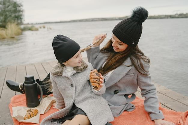 Modische mutter mit tochter. leute auf einem picknick. frau in einem grauen mantel. familie am wasser. Kostenlose Fotos