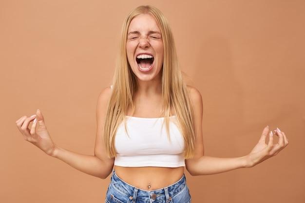 Modische teenager-mädchen mit blonden haaren trägt jeans und weißes top schreien Kostenlose Fotos