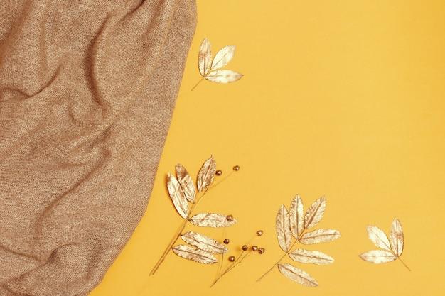 Modischer gestrickter schal und goldenes herbstlaub auf gelbem papier Premium Fotos
