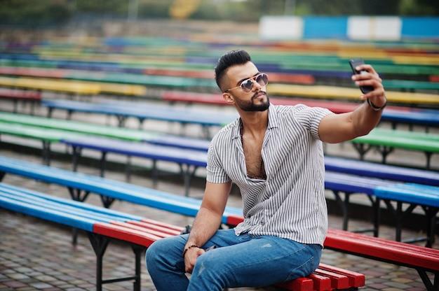 Modischer großer bärtiger mann, der hemd, jeans und sonnenbrille trägt, die auf farbigen sitzreihen sitzen und sein telefon benutzen Premium Fotos