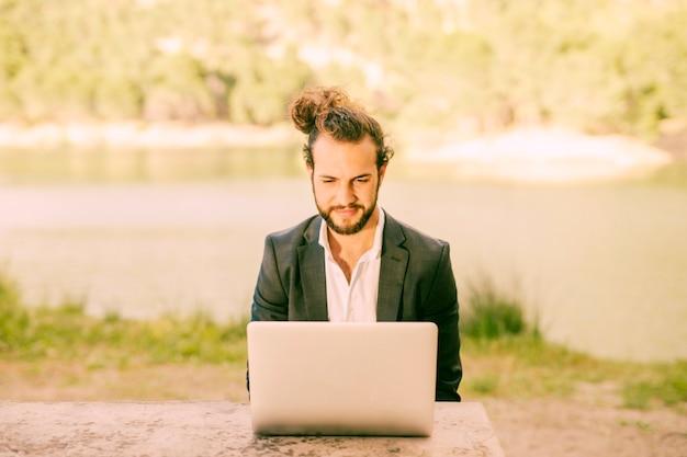 Modischer mann, der draußen mit laptop arbeitet Kostenlose Fotos