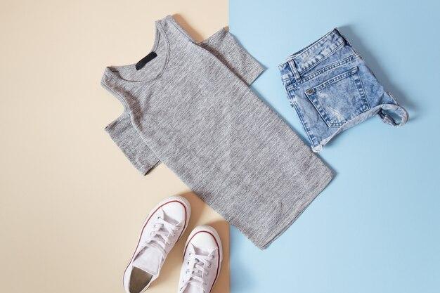 Modisches konzept. urbaner frauenstil. graues t-shirt, weiße turnschuhe und kurze jeanshose auf einem weichen blauen hintergrund Premium Fotos