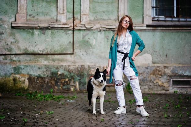 Modisches mädchen an den gläsern und an zerrissenen jeans mit russisch-europäischem hund laika (heiser) an einer leine, gegen straße der stadt Premium Fotos
