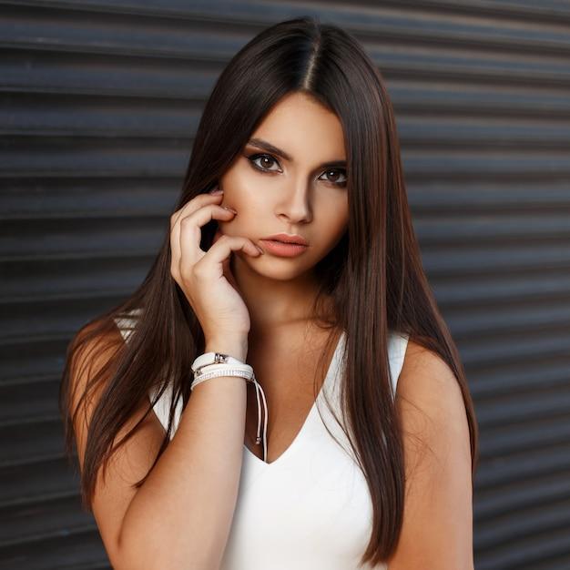 Modisches porträt einer schönen jungen frau mit make-up in einem weißen kleid nahe einer dunklen metallwand Premium Fotos