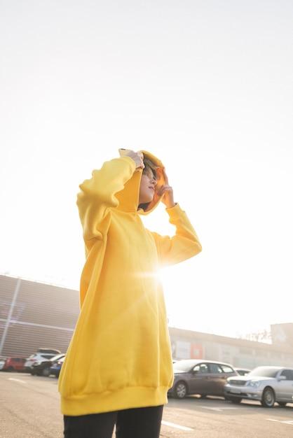 Modisches straßenporträt eines mädchens in einem gelben kapuzenpulli Premium Fotos