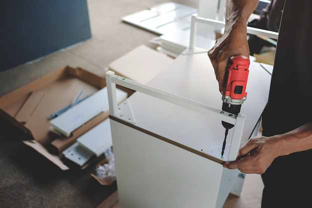 Möbel zu hause zusammenbauen. umzug in ein neues haus oder ein diy-konzept. handwerker, der einen kabellosen schraubendreher verwendet, um das gehäuse zu installieren. Premium Fotos