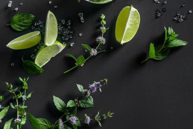 Mojito cocktail zutaten auf dunkel: limette, minze und crushed ice Premium Fotos