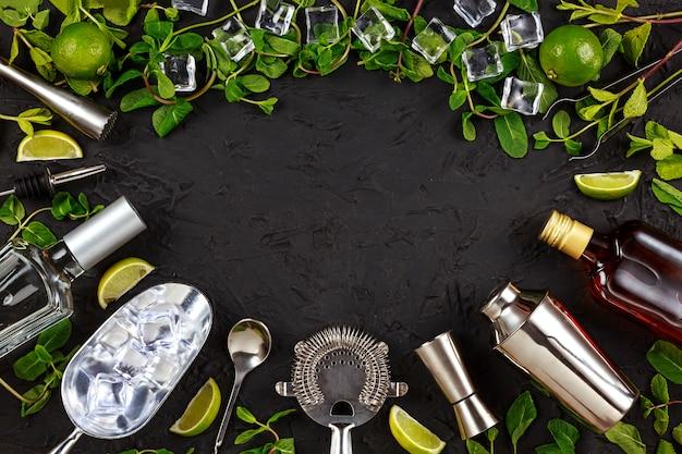 Mojito. rahmen von barwerkzeugen und produkten für die zubereitung von cocktails. platz sparen. minze, limetteneis, rum, soda, tequila Premium Fotos