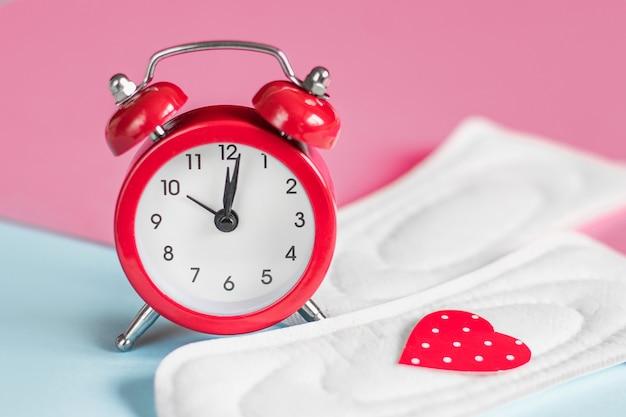 Monatsauflagen, roter wecker auf einem rosa hintergrund. menstruationsperiode-konzept. menstruationsverzögerung konzept Premium Fotos