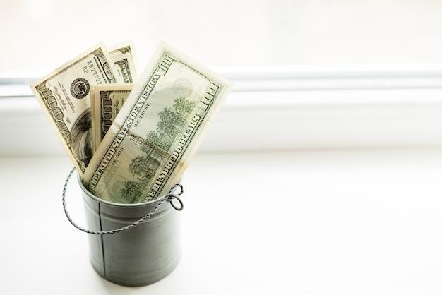 Moneybox, dollar im eimer auf weißem fenster heller hintergrund Premium Fotos