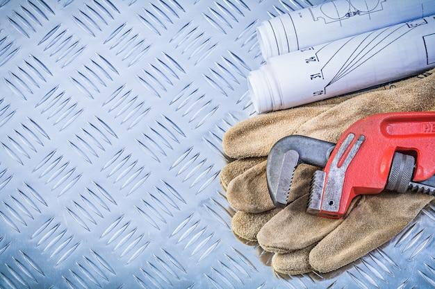 Monkey wrench blaupausen sicherheitshandschuhe auf gerilltem metallhintergrundkonstruktionskonzept Premium Fotos