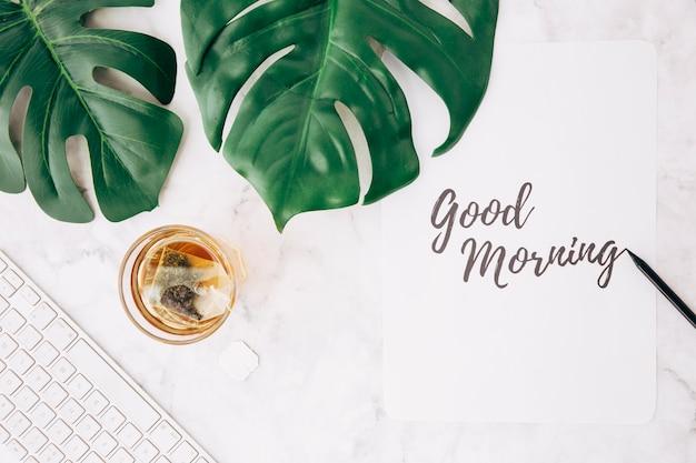 Monstera blatt; teebeutel aus transparentem glas; tastatur und handschriftlicher text des guten morgens auf papier über dem strukturierten hintergrund Kostenlose Fotos