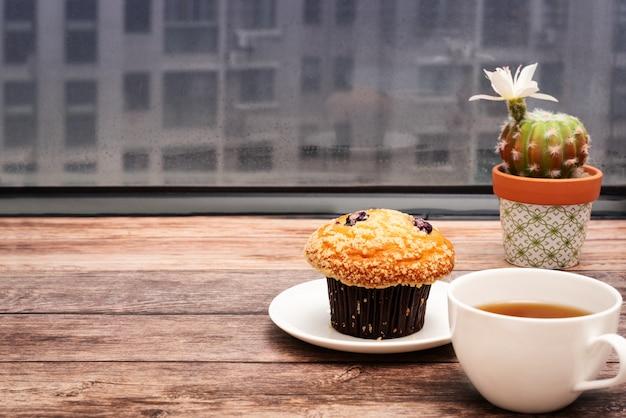 Montag-morgen-konzept, heißer tee und muffinkuchen auf hölzernem arbeitsplatz Premium Fotos