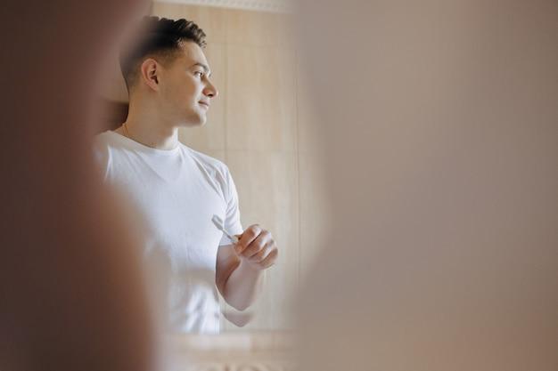 Morgen hygiene putzt der junge seine zähne in der nähe des spiegels Premium Fotos