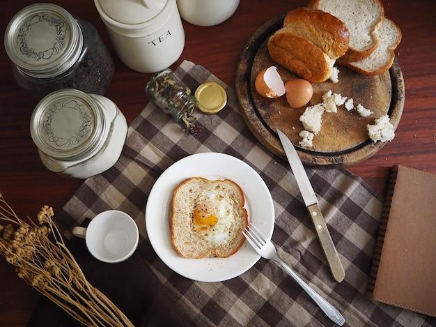 Morgen tisch frühstück mit brot und ei mit einer tasse tee auf braun karierten tischdecke Premium Fotos