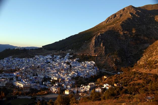 Morgendämmerung über der stadt chefchaouen marokko. die sonnenstrahlen erhellen die hänge der berge und die dächer der häuser. blaue stadt Premium Fotos