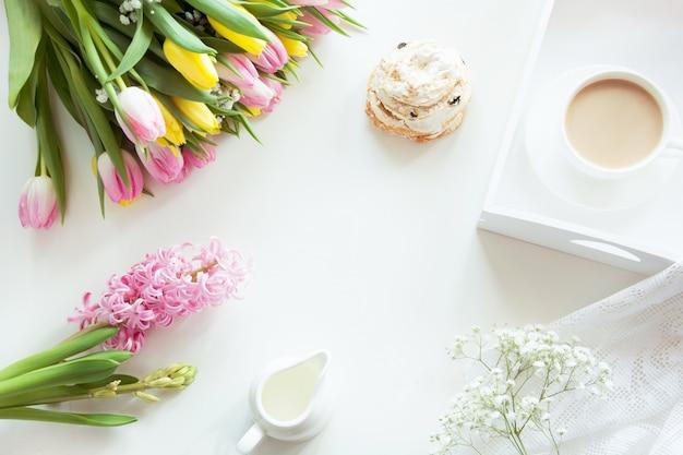 Morgenfrühstück im frühjahr mit einer tasse schwarzen kaffee mit milch und gebäck in den pastellfarben Premium Fotos