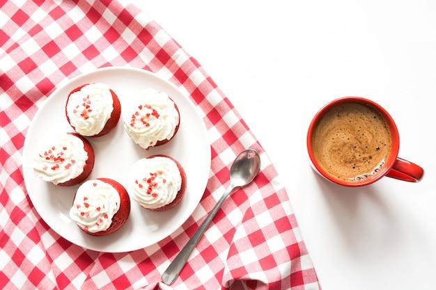 Morgenfrühstück mit schale schwarzem kaffee und fünf roten samtkleinen kuchen auf weiß. ansicht von oben. Premium Fotos