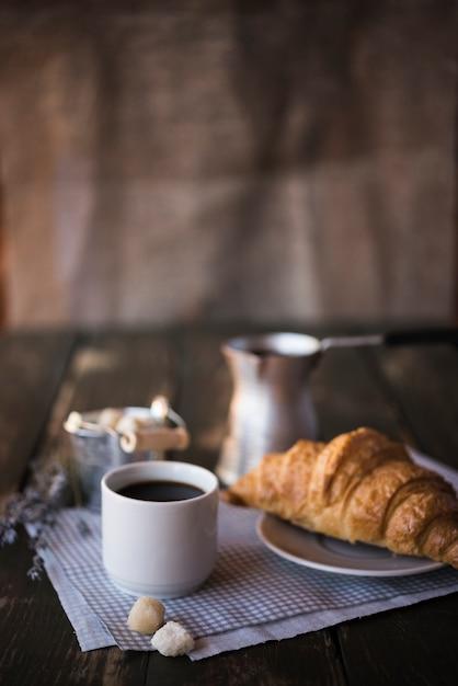 Morgenfrühstückskaffee und -hörnchen auf kopienraumhintergrund Kostenlose Fotos