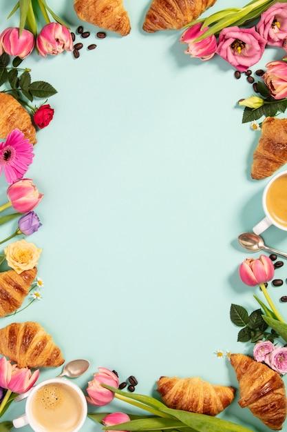 Morgenkaffee, hörnchen und schöne blumen. flach liegen Premium Fotos