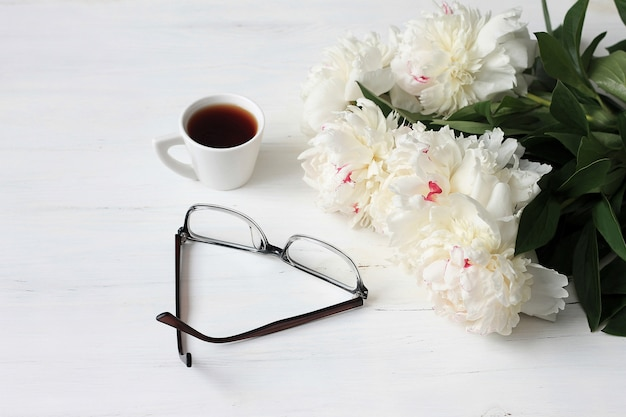 Morgenkaffeetasse, gläser und weiße pfingstrosen blüht auf weißem holztisch Premium Fotos