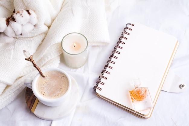 Morgenkaffeetasse mit notizbuch, kerze und baumwollblumen auf einer draufsicht des weißen betts Premium Fotos