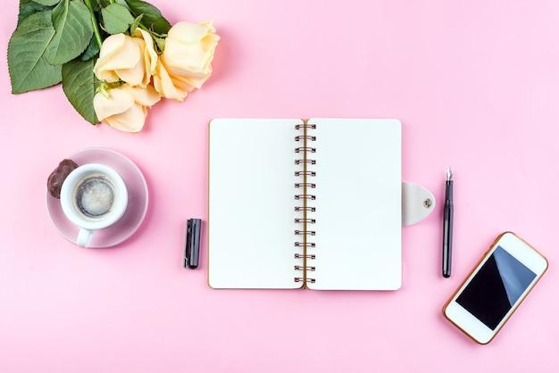 Morgenkaffeetasse zum frühstück, ephone, notizbuch, bleistift und stieg auf rosa tabelle Premium Fotos