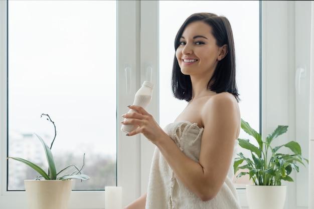 Morgenporträt der jungen lächelnden frau im badtuchtrinkmilch-getränkjoghurt von der flasche Premium Fotos
