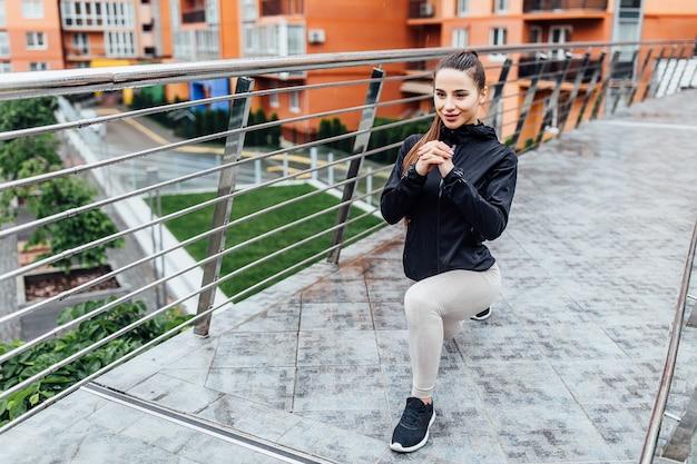 Morgens. junge, brunette trägt die frau zur schau, die beine auf der treppe in der modernen stadt ausdehnt. gesunder lebensstil in der großstadt. Premium Fotos