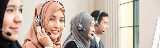 Moslemische frau, die als kundendienstbetreiber mit team im kundenkontaktcenter arbeitet Premium Fotos