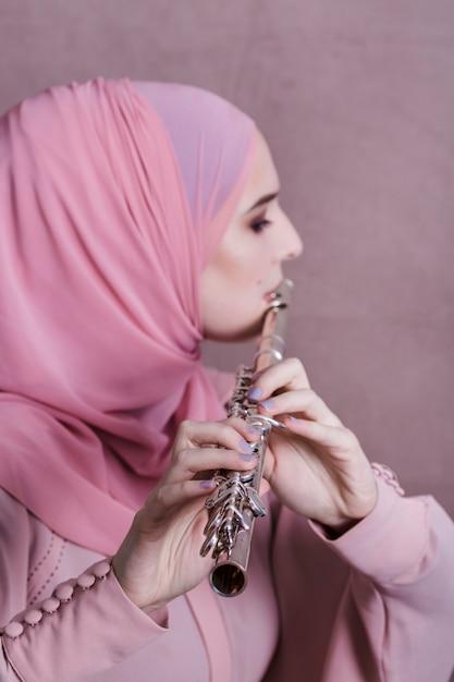 Moslemische frau, die auf der flöte spielt Kostenlose Fotos