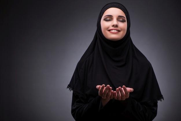 Moslemische frau im schwarzen kleid gegen dunklen hintergrund Premium Fotos