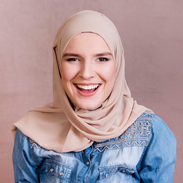 Moslemische frau mit kopftuch lachend vor farbigem hintergrund Premium Fotos
