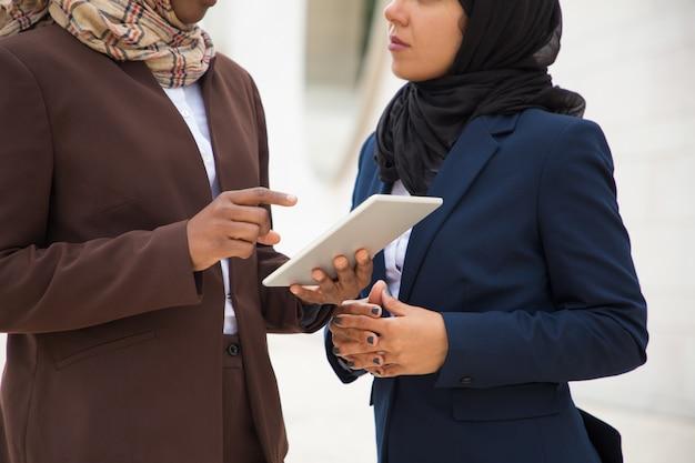 Moslemische geschäftsfrauen, die zusammen digitale tablette verwenden Kostenlose Fotos