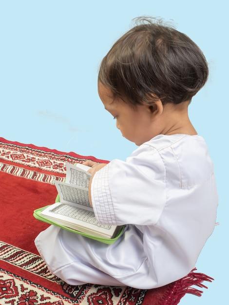 Moslemischer junge in einem kleid den koran lesend Premium Fotos