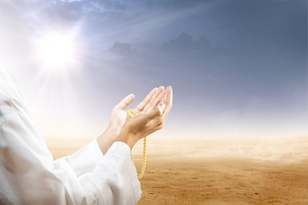 Moslemischer mann, der mit gebetsperlen auf seinen händen in der wüste betet Premium Fotos