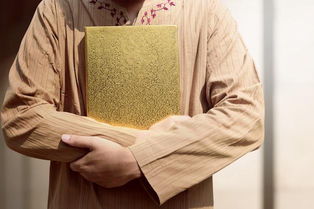Moslemischer mann, der quran hält Premium Fotos