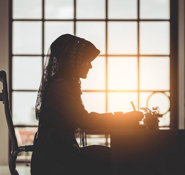 Moslemisches geschäftsleute konzept - schattenbild der islamfrau arbeitend an bürotischfenster-morgenaufflackern Premium Fotos