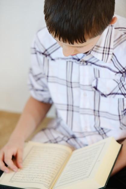 Moslemisches kind, das koran liest Premium Fotos