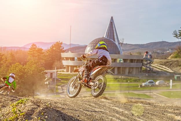 Moto cross biker beim rennen - eine scharfe kurve und der sprühnebel von schmutz, rückansicht - nahaufnahme Premium Fotos