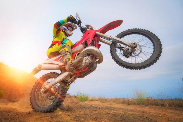Motocross-fahrer macht einen wheelie Premium Fotos