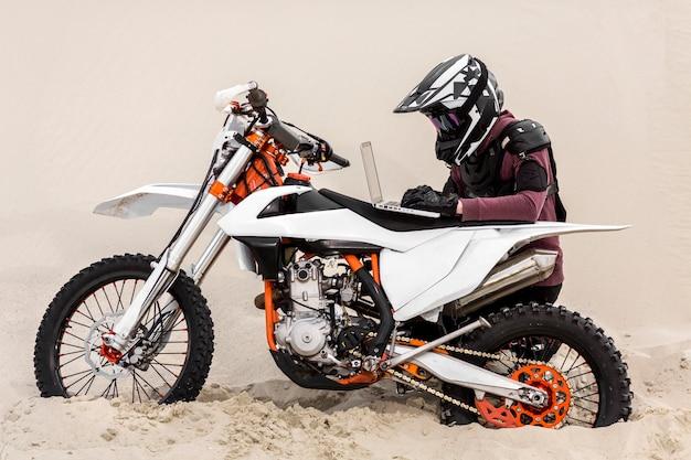 Motorradfahrer, der laptop in der wüste durchsucht Kostenlose Fotos