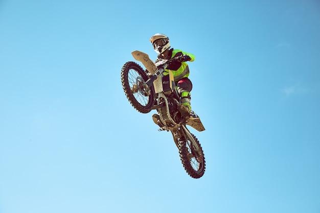 Motorradfahrer fliegen am blauen himmel. extremes konzept, weitsprung auf einem motorrad. Premium Fotos