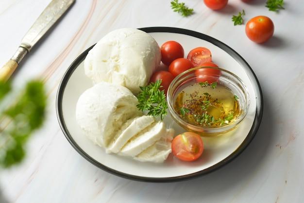 Mozzarella-käse und kirschtomaten mit gewürzen. hausgemachter mozzarella. Premium Fotos