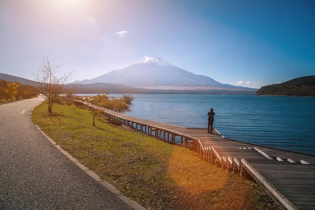 Mt. fuji über see kawaguchiko mit herbstlaub und reisendfrau bei sonnenaufgang in fujikawaguchiko, japan. Premium Fotos