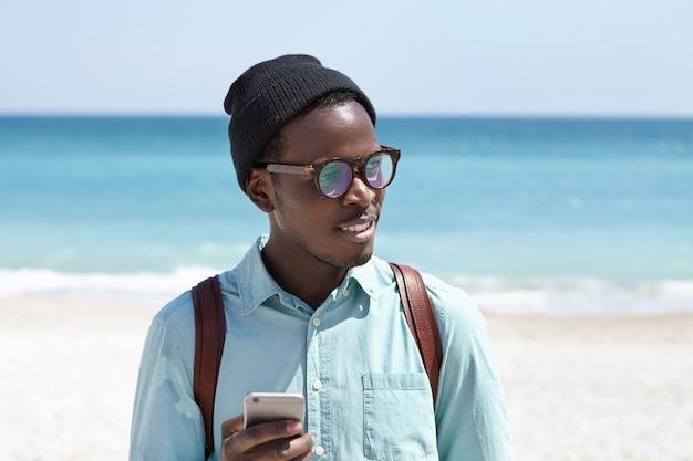 Müde afroamerikanische rucksacktouristen in hut und brille, die die online-taxi-service-app auf dem handy verwenden, um ein taxi anzufordern, während sie sich durstig fühlen und nach einem ort suchen, an dem sie ein kaltes getränk trinken können Kostenlose Fotos